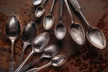 Old metal spoons on rusted background