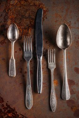 Vintage spoons and forks with knife on rusted background