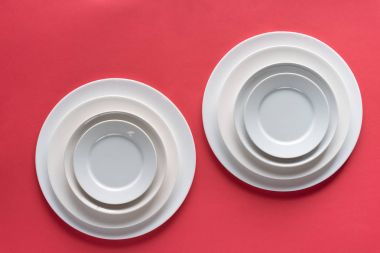 White plates of different sizes on red background