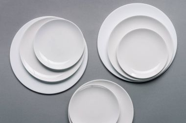 Composition of white plates on grey background