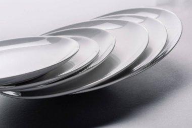 White ceramic plates stacked on white table