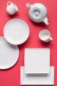 Fotografie Bílé nádobí talíře a čaj set na červeném pozadí