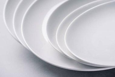 White ceramic plates stacked on white background