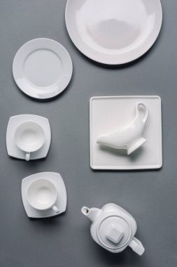 White plates with teapot and cups on grey background