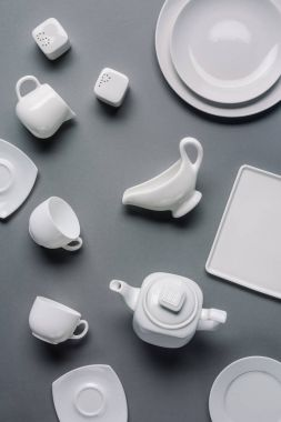 White tableware for dinner and tea time on grey background