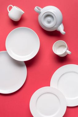 White plates with teapot and cup on red background