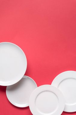 Composition of white plates on red background