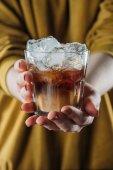 Fényképek részleges kilátás nyílik üveg hideg kávé, jégkocka tartó kezében női