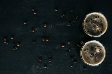 top view of glasses of cold brewed coffee with ice on dark surface with roasted coffee beans around