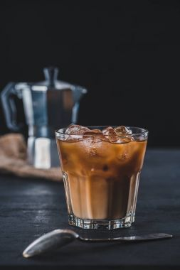 selective focus of glass of cold iced coffee and coffee maker on tabletop on dark backdrop