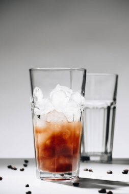 close up view of glass of cold brewed coffee with ice cubes and roasted coffee beans on grey background