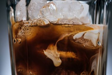 close up view of cold brewed coffee with ice cubes in glass