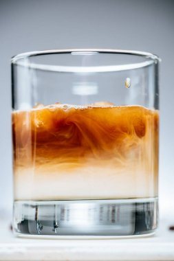 close up view of cold iced coffee with milk in glass on grey background