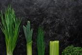 pohled shora zelené cibule, pór a pažitka na konkrétní stůl, zdravé stravovací koncept
