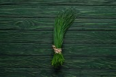 Fotografie top view of bunch of chives on wooden table, healthy eating concept