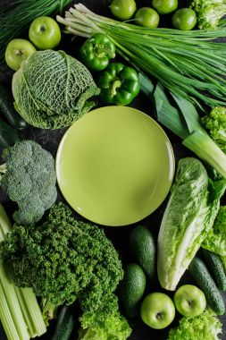 top view of green plate between green vegetables, healthy eating concept