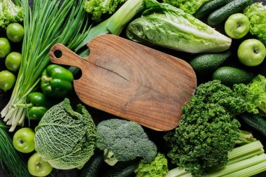 top view of wooden board between green vegetables, healthy eating concept