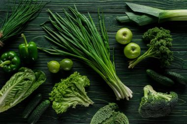 top view of green onion, apples and broccoli on wooden table, healthy eating concept