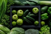top view of apples and cucumbers in wooden box between green vegetables, healthy eating concept