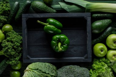top view of green bell peppers in wooden box between vegetables, healthy eating concept