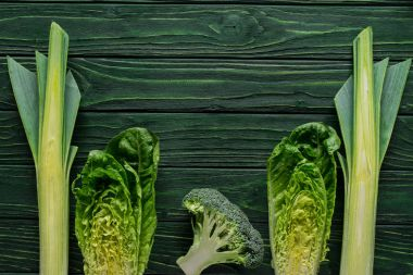 top view of green leek, cabbage and broccoli on wooden table, healthy eating concept