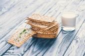 Fotografie křupavé sušenky s tvarohem a sklenice mléka na dřevěný stůl
