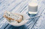 Fotografie Detailní pohled tvaroh v misce, sušenka a sklenice mléka na dřevěný stůl