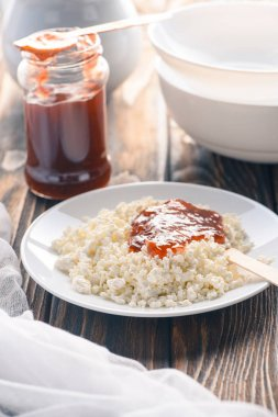 tasty healthy cottage cheese with jam on wooden table