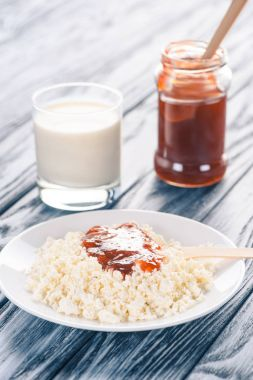 close-up view of delicious cottage cheese with jam and glass of milk on wooden table