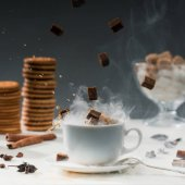 Close-up of brown sugar cubes falling into coffee cup with splashes