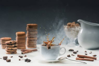 White cup of hot steaming coffee with splashing sugar cubes on table with cookies and spices