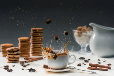 Cane sugar cubes splashing in cup with hot black coffee in front of biscuits and spices