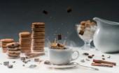 Barna cukor kockákra esik csésze fekete kávé táblázat a cookie-k és a fűszerek