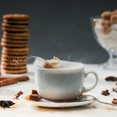 Fotografie Brown sugar cubes splashing into coffee cup on table with cookies and spices