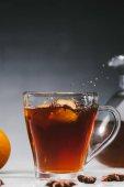 Horký černý čaj v šálku s kousky citrónu a postříkání