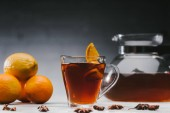 Hot black tea in cup with lemons and oranges