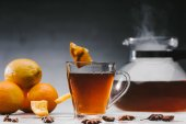 Black tea in cup with lemons and star anise on table