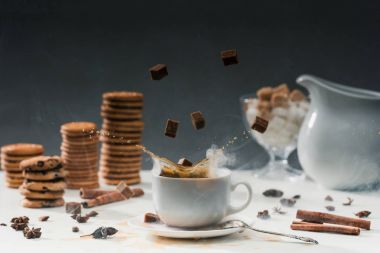 Coffee cup with splashing cane sugar on table with cookies and spices