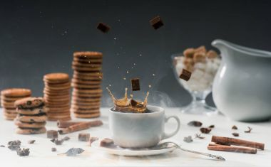 Brown sugar cubes falling in cup with black coffee on table with cookies and spices