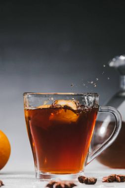 Hot black tea in cup with lemon pieces and splashes