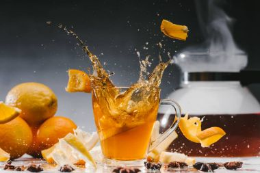 Large splashes of tea in glass cup with citruses and spices