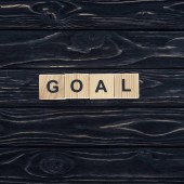 top view of word goal made of wooden blocks on dark wooden tabletop