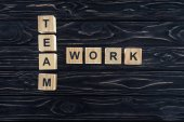 top view of team work words made of wooden blocks on dark wooden tabletop