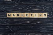 Photo top view of word marketing made of wooden blocks on dark wooden tabletop