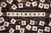 Fotografie top view of of word statements made of wooden blocks on wooden surface