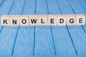 Photo close up view of knowledge word made of wooden blocks on blue tabletop