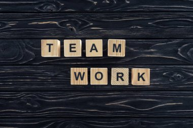 top view of word team work made of wooden blocks on dark wooden tabletop