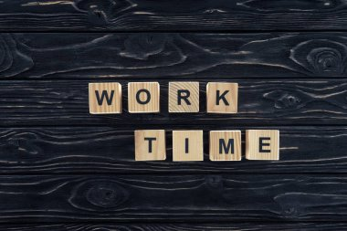 top view of work time words made of wooden blocks on dark wooden tabletop