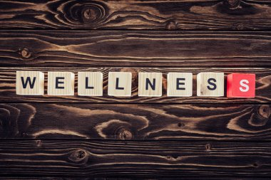 top view of wooden blocks arranged in wellness word in brown wooden surface