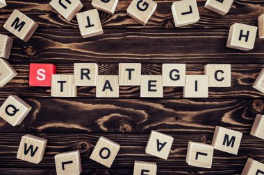 top view of strategy inscription made of wooden blocks on brown wooden surface